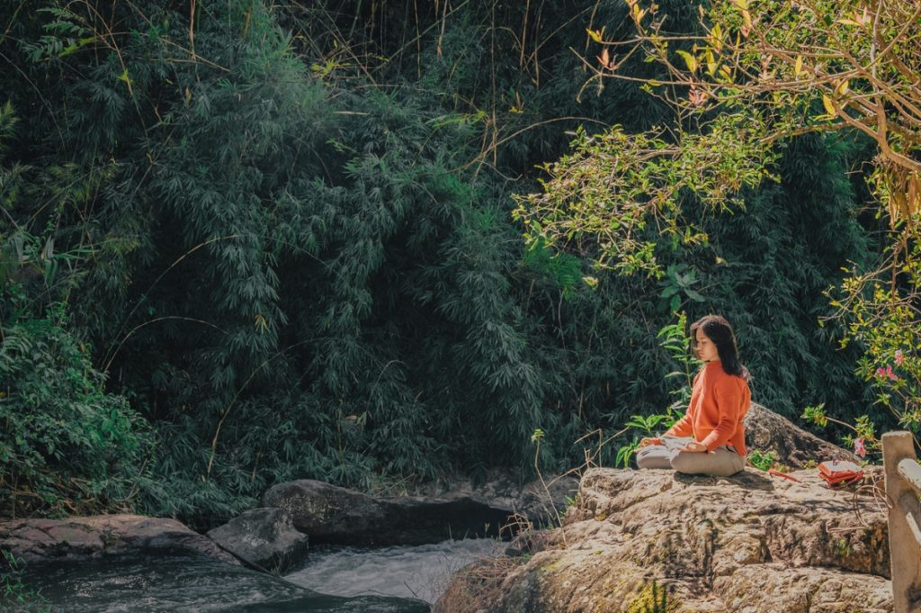 A woman practicing yoga by the river on a forest